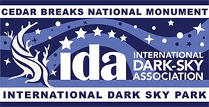 "Blue and white logo saying ""international dark sky park"" with bristlecone and stars."