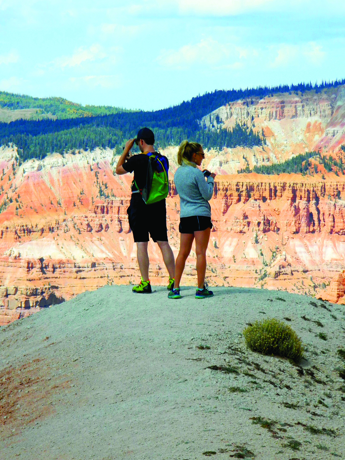 Young man and woman photographing pink scenic cliffs from an overlook.