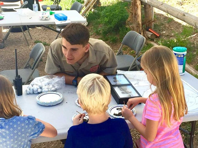 Kids with park employee dissecting owl pellets.