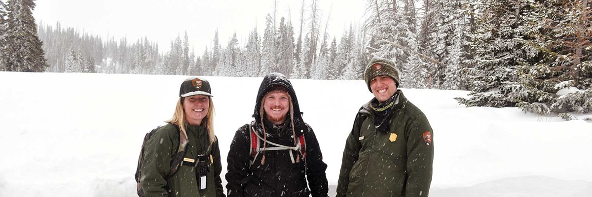 Two rangers and a red headed man standing in a snowy field.