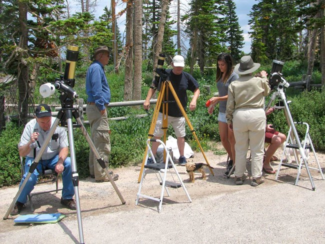 Group of people setting up and looking through three telescopes during the day.