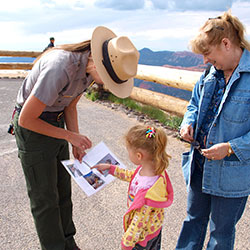 Ranger showing information to a child and her mother.