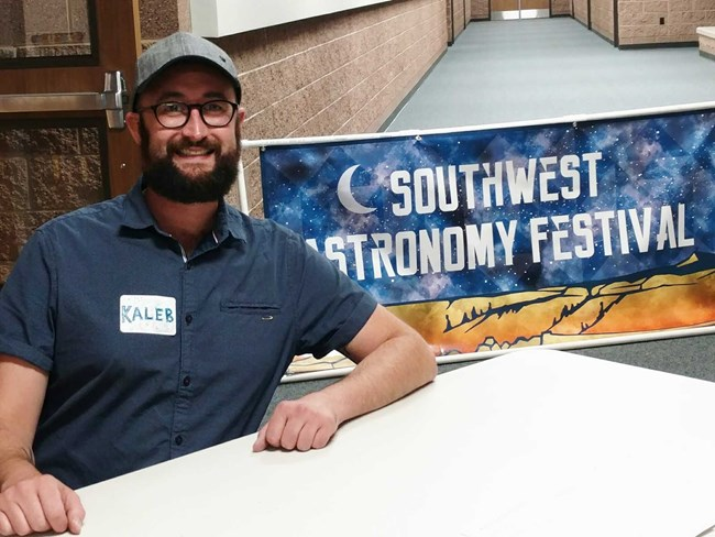 "Man with beard sitting at desk with sign saying ""SW astronomy festival"" in background."