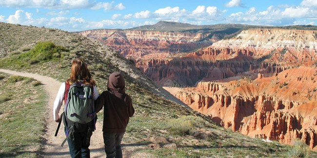 Two people hiking along the cliff rim of Cedar Breaks.