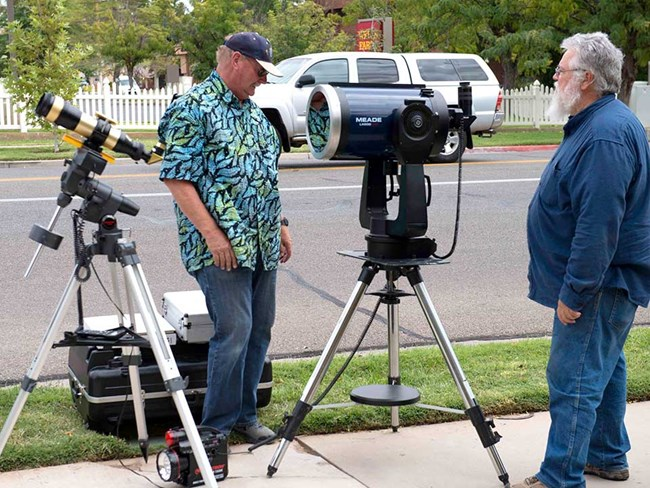 Two older gentlemen with telescopes.