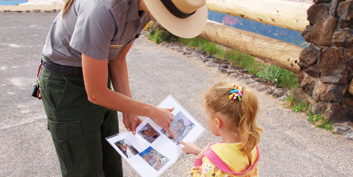 Ranger showing a small child photos about Cedar Breaks.