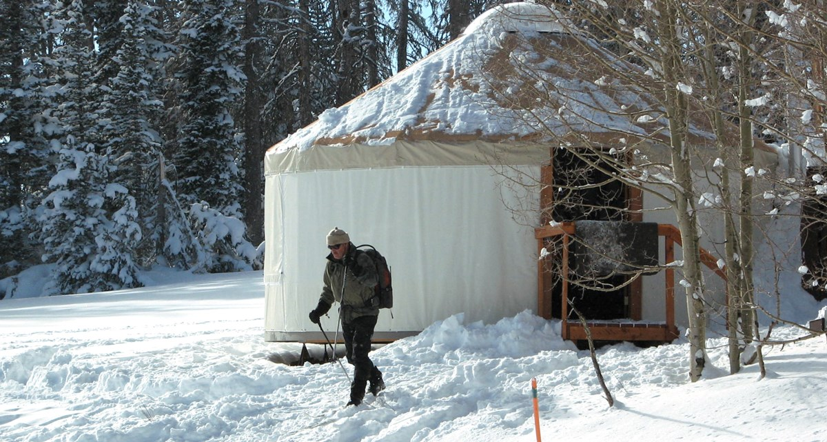 Man skiing away from winter yurt