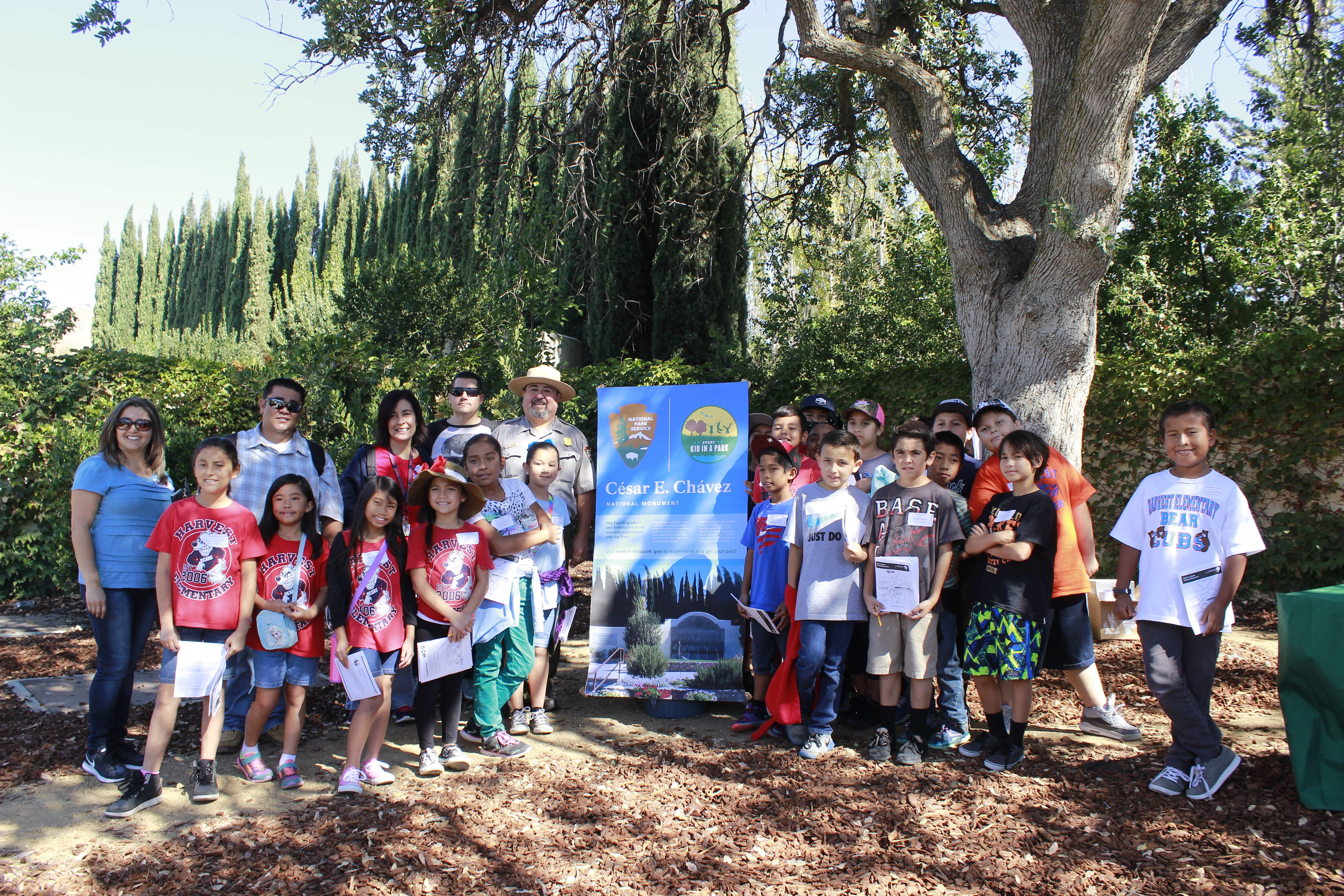 students, teachers and park superintendent pose under a tree