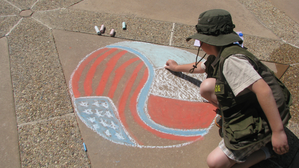 rear view of child drawing on pavement in chalk