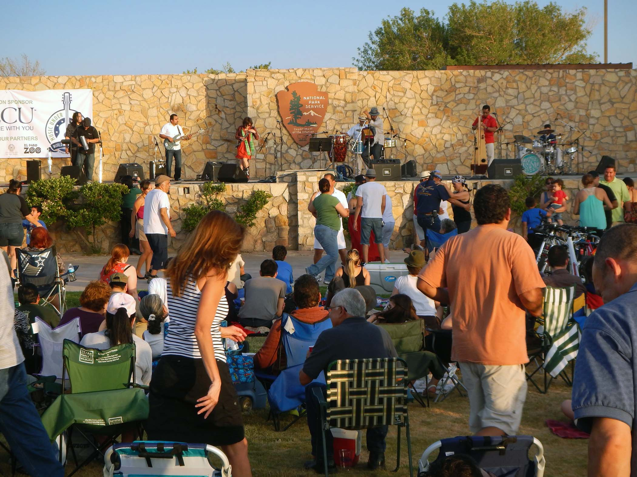 the back of a large group of people, some sitting in lawn chairs and some dancing, in front of amphitheater with band onstage