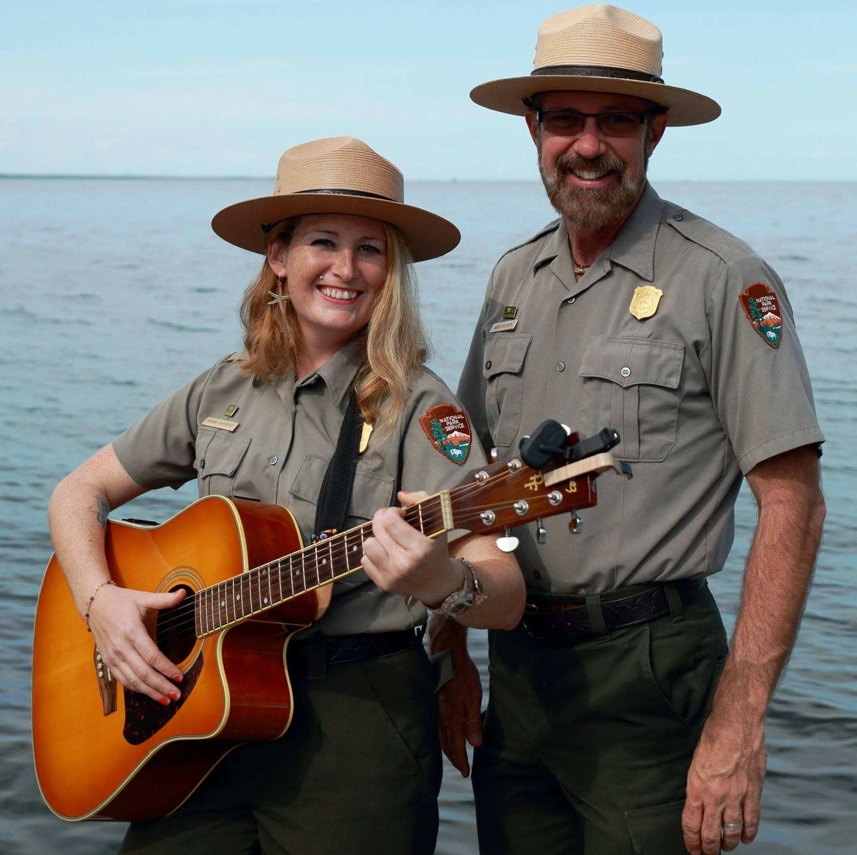 Woman holding guitar and man, both in park ranger uniforms