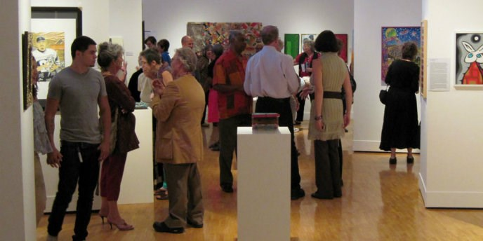 Small crowd of people looking at paintings on gallery walls