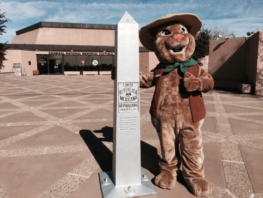 spotted ground squirrel ranger mascot standing next to boundary marker in front of building