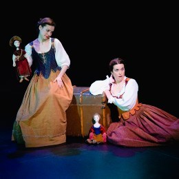 two actresses in period costume with puppets
