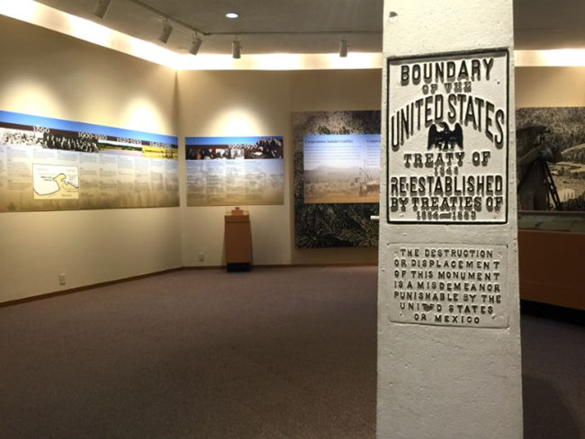 Boundary monument placard in foreground with exhibit walls in background