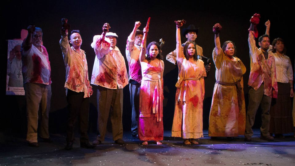 actors portray a group of people covered in blood raising fists with weapons