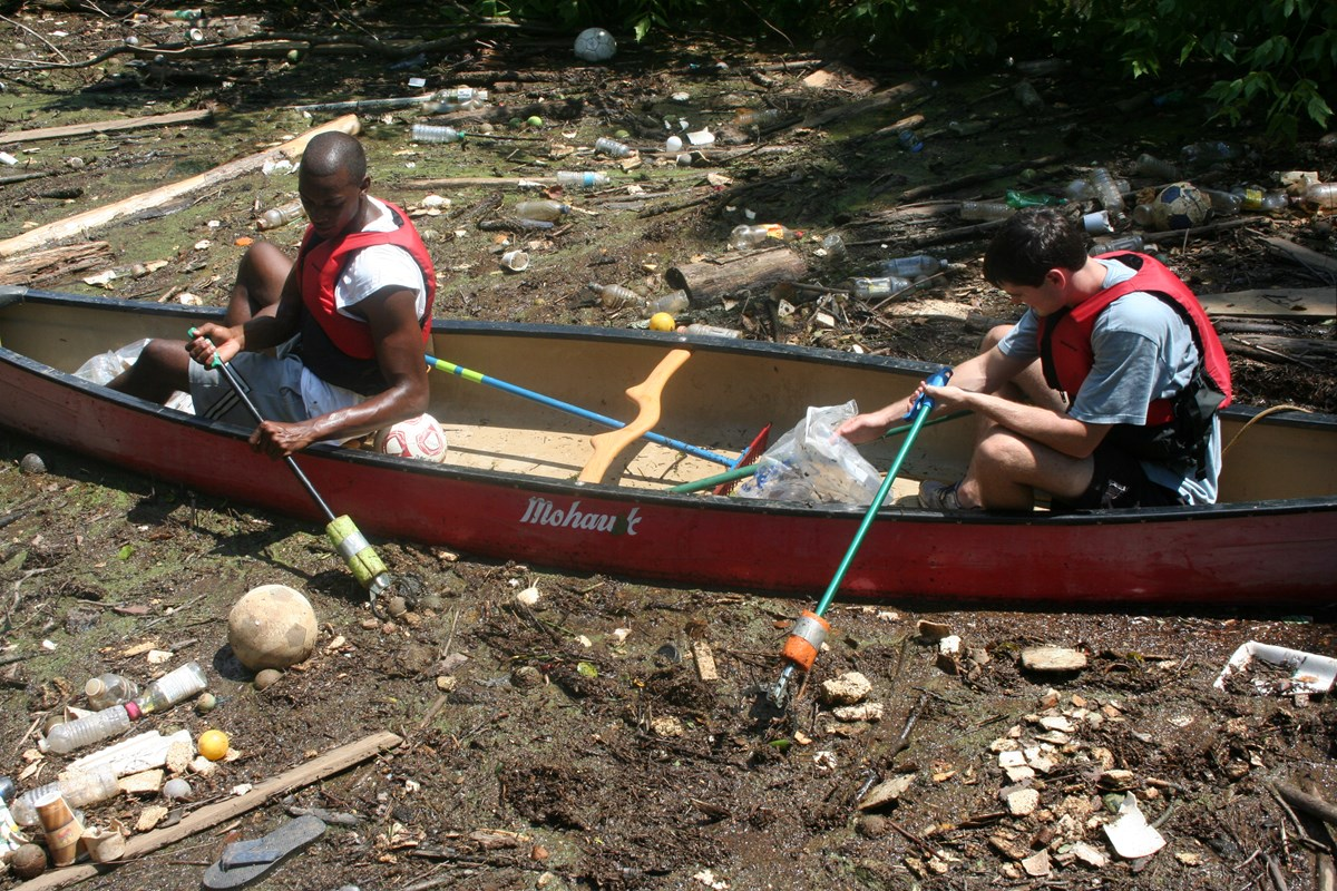 Two paddlers in canoe picking trash out of the Chattahoochee River.