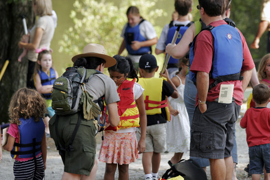 Park ranger helps a young boater buckle her PFD at a festival.