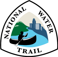 National Water Trail System official logo showing solo canoest paddleing down river with green hills to the left and urban skyline to the right.