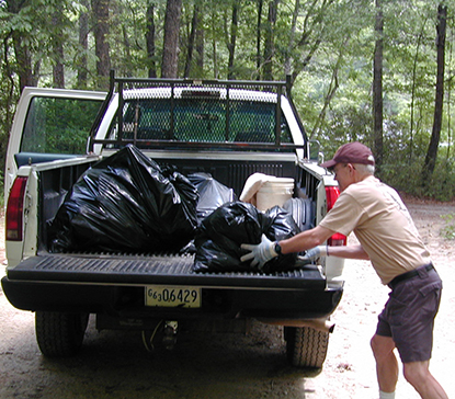 A volunteer loads bags of trash into a pickup.