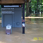 River water floods entrance fee station and wooded picnic area.