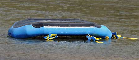 Capsized raft on the river with empty PFDs.