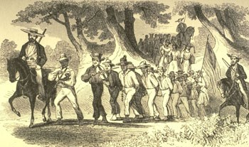 A group of enslaved people chained together and escorted by white men on horseback