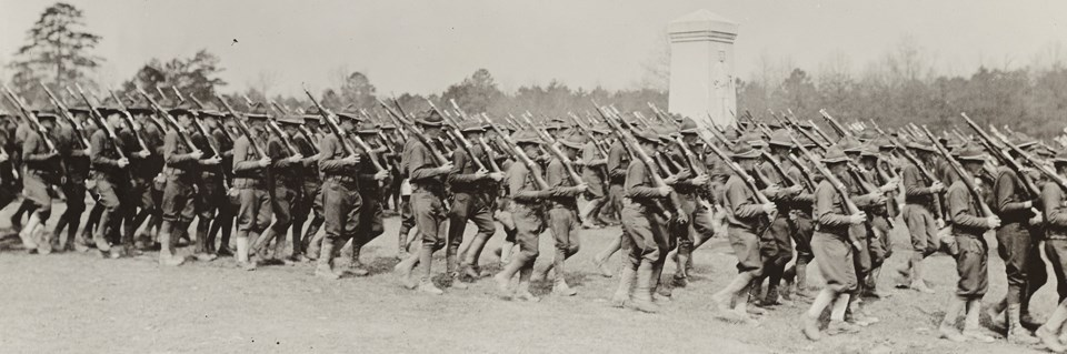 World War I soldiers marching in front of a monument