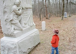 A junior ranger ranger standing in front of a stone monument