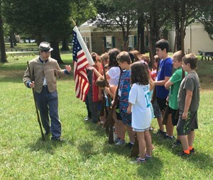 A park ranger wearing a confederate uniform leads a program for a small group of students.