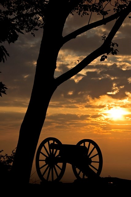 Cannon by tree on cliff overlooking Chattanooga with sunset in background.