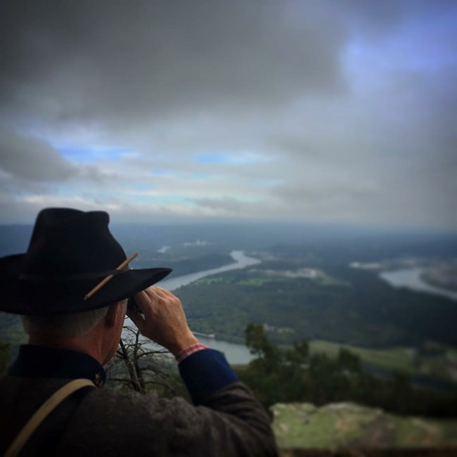 A Confederate officer looks through his binoculars toward Union artillery on Moccasin bend