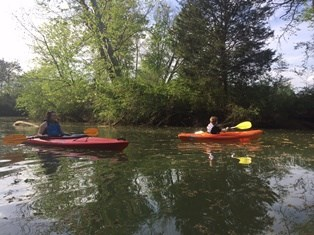 Two kayakers paddle West Chickamauga Creek near the park boundaries.