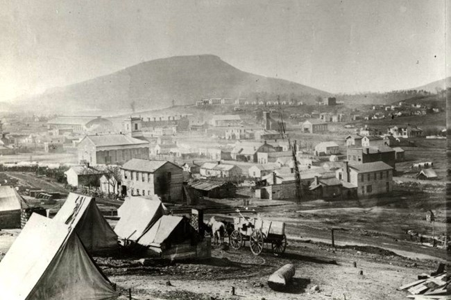 Chattanooga as it appeared in 1864 with dirt streets and Lookout Mountain looming in the background.