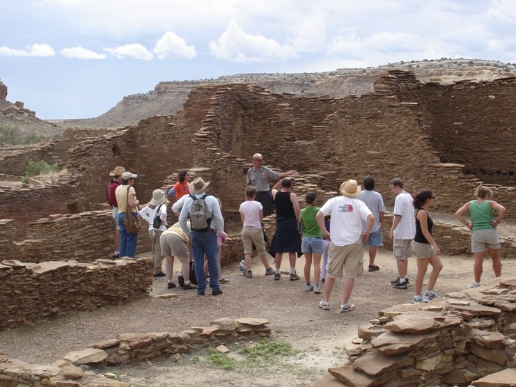 Photo of Park Ranger Kirk Prtrtson with visitors at Pueblo Bonito