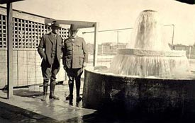 Two men standing next to an artesian well