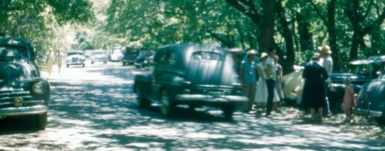 1940s cars and visitors along a crowded roadway