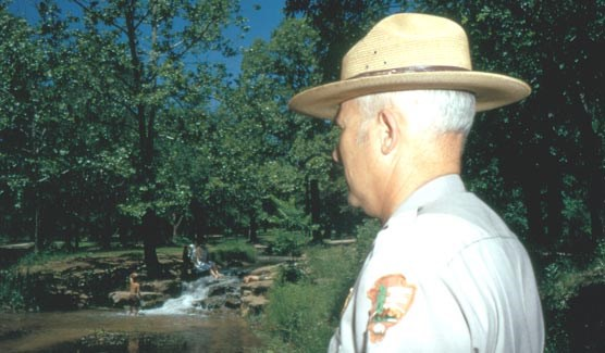 Park ranger observing visitors swimming, circa 1970