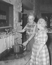 Man and woman dispensing mineral water