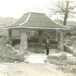 Stone and wood pagoda-style pavilion over a mineral spring