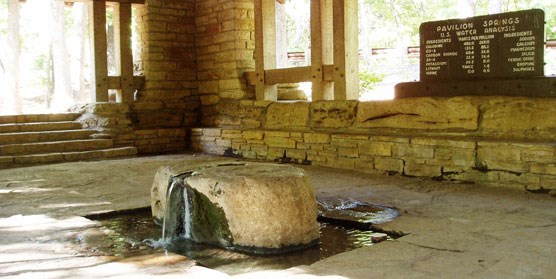 Interior of stone spring pavilion with water coming out of a large boulder