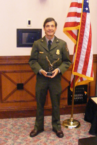 Park ranger in uniform holding an award