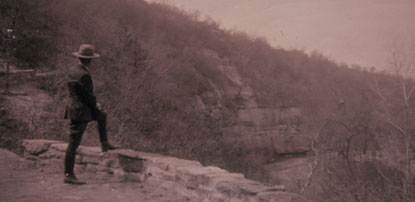 Old photo of a park ranger standing on a trail, looking into the distance