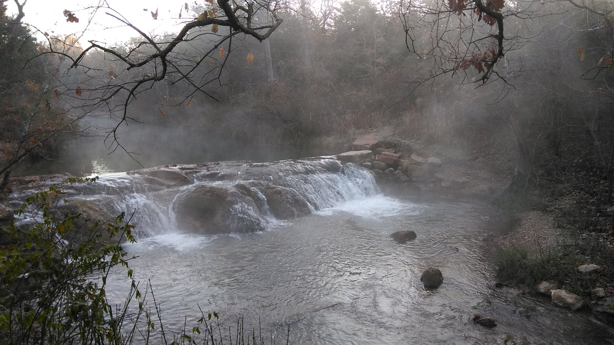 A small waterfall surrounded in mist on a winter morning.