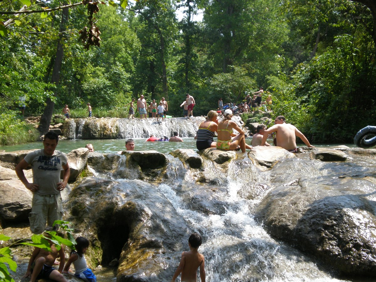 Approximately 30 people in the water in a creek with a small wide waterfall.