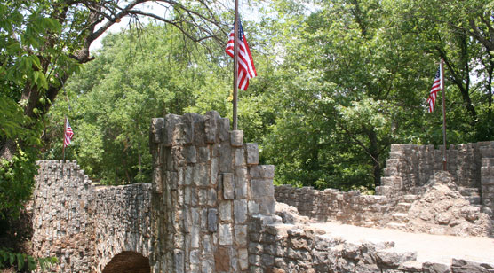 American flags fly on the turrets of a stone bridge