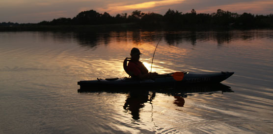 Fisherman in a kayak reflected in the setting sun
