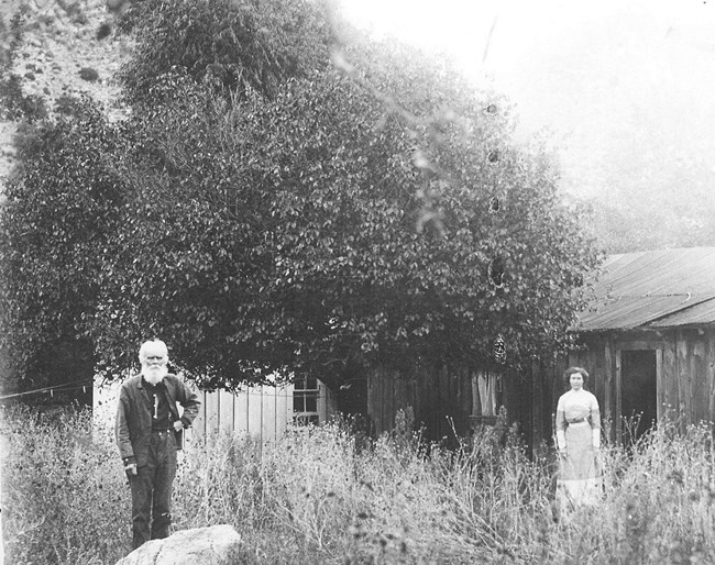 Black and white photo of an older man with a white beard and a young woman standing in front of a log cabin.