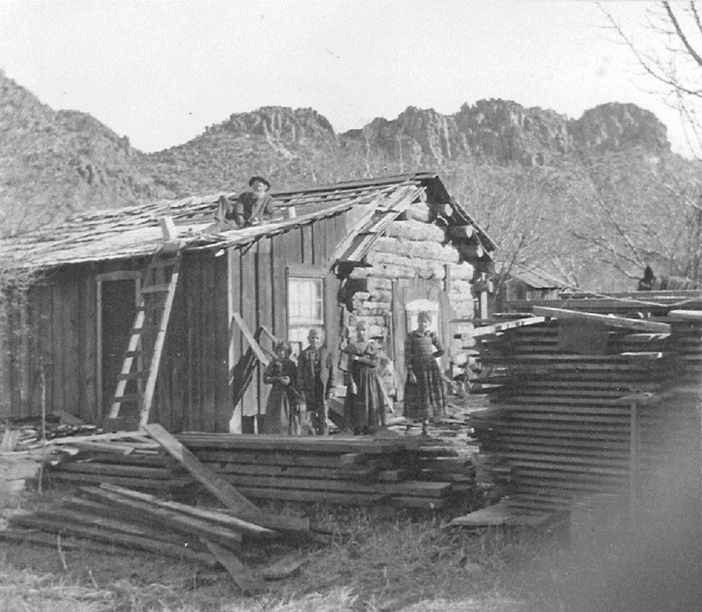 Black and white photo of man on log cabin roof, surrounded by building material and four children standing by piles of lumber.