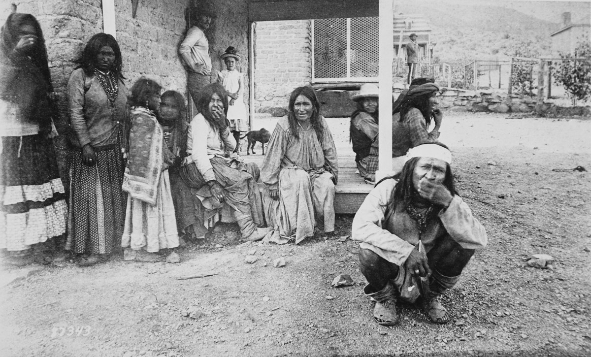 Black and white photograph of Chiricahua Apache at Fort Bowie. Many are sitting on a porch or leaning against an adobe building, and one man is squatting on the ground, wearing a headband with his hand over his mouth.